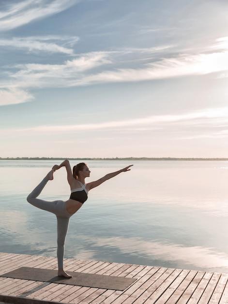 De sportdame die zich bij het strand bevindt maakt yogaoefeningen. Gratis Foto