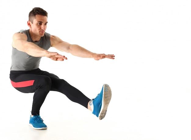 De sportenmens doet hurkende training in studio Premium Foto