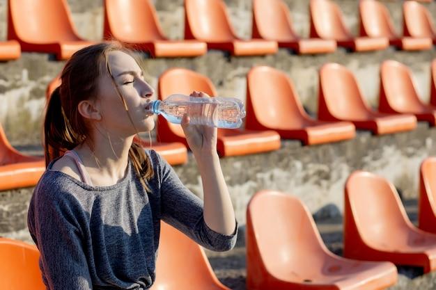 De sportieve jonge aantrekkelijke vrouw in sportkleding het ontspannen na harde training zit en drinkt water van speciale sportfles na het lopen op een stadion Premium Foto