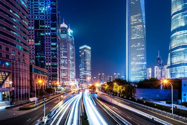 De stadsgebouwen van shanghai bij nacht en vage autolichten Premium Foto