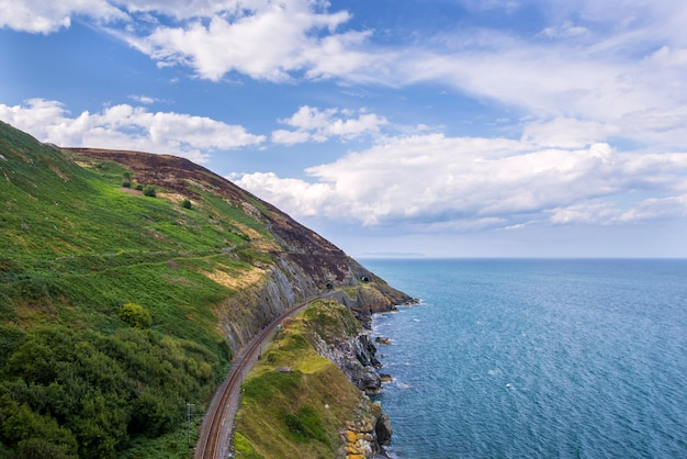 De steen schommelt bergweg en spoorweg bij ierse zeekust. bray, greystone Premium Foto