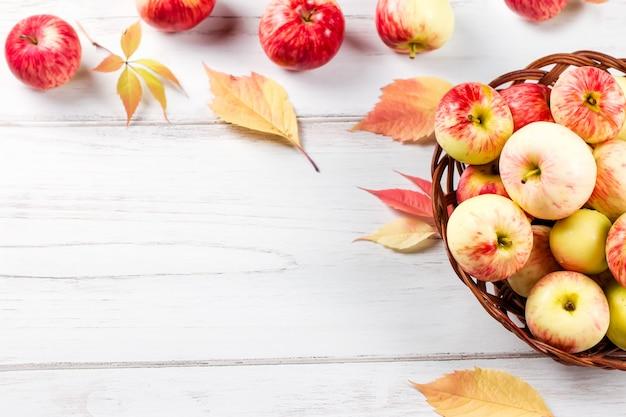 De stemming van de herfstsamenstelling met rode appelen in rieten mand en gele bladeren Premium Foto