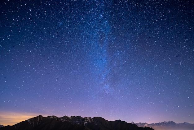 De sterrenhemel in de kersttijd en de majestueuze hoge bergketen van de italiaanse franse alpen Premium Foto