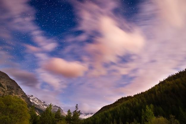 De sterrenhemel met wazig bewegende wolken en fel maanlicht Premium Foto