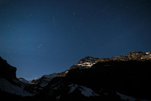 De sterrenhemel op de alpen verlicht door maanlicht. Premium Foto