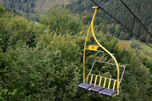 De stoelen van de kabelbaan op de achtergrond van de berg makovitsa, een van de karpaten Premium Foto