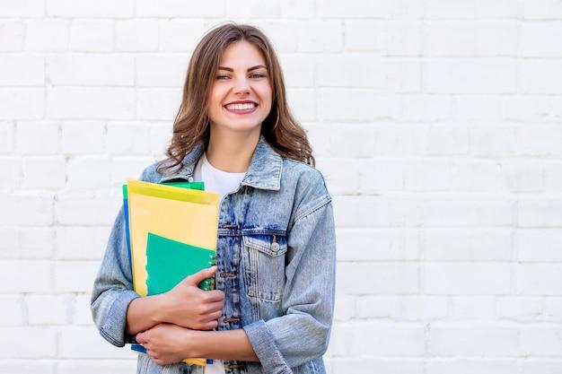De studente houdt omslagen en een notitieboekje in haar handen en glimlacht op een achtergrond van een witte bakstenen muur, exemplaarruimte Premium Foto
