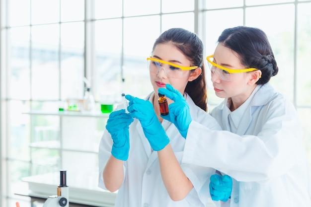 De studentenstudenten die van de close-upwetenschap met chemische producten in laboratorium werken Premium Foto