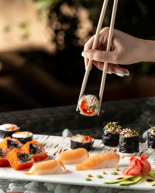 De sushibroodje van de vrouwenholding met eetstokjes Gratis Foto