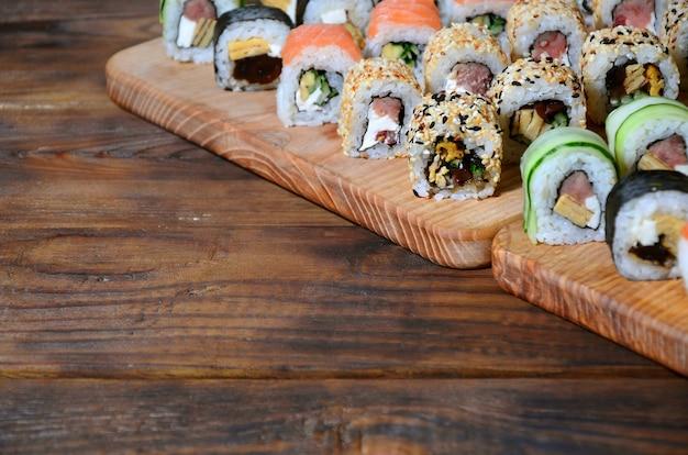 De sushireeks van een aantal broodjes wordt gevestigd op een houten scherpe raad op een lijst in de keuken van een sushistaaf. Premium Foto