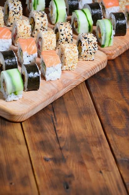 De sushireeks van een aantal broodjes wordt gevestigd op een houten scherpe raad op een lijst in de keuken van een sushistaaf Premium Foto