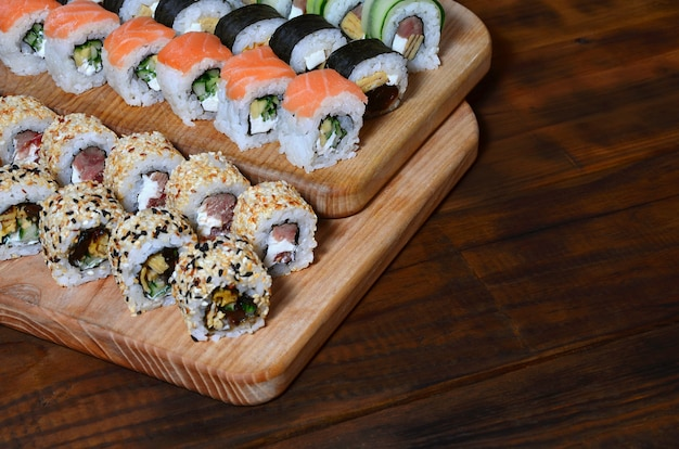 De sushireeks van een aantal broodjes wordt gevestigd op een houten scherpe raad op een lijst in de keuken Premium Foto
