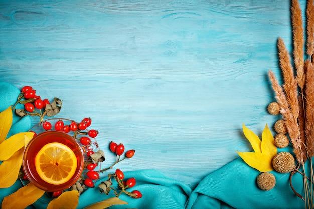 De tafel, versierd met herfstbladeren, bessen en verse thee. herfst. herfst achtergrond. Premium Foto