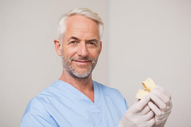 De tandarts in blauw schrobt houdend mondmodel Premium Foto