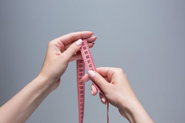 De tape in vrouwelijke handen op grijze ruimte. gewichtsverlies, dieet Gratis Foto