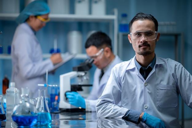 De teamwerkspecialist scientis of onderzoeker test en ontwikkelt het experiment van het medicijn tegen chemisch vaccin microscopisch in het moderne biologische laboratorium Premium Foto