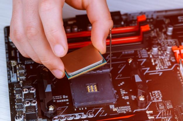 De technicus plaatst de cpu op de aansluiting van het moederbord van de computer. Premium Foto