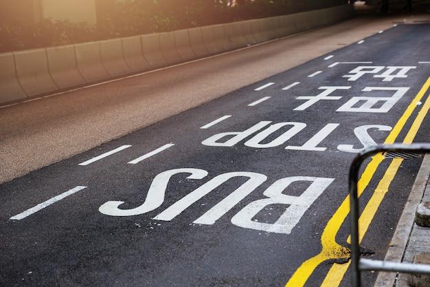 De tekst van het bushalteteken op de weg in hong kong Premium Foto