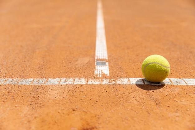 De tennisbal van de close-up op hofgrond Gratis Foto
