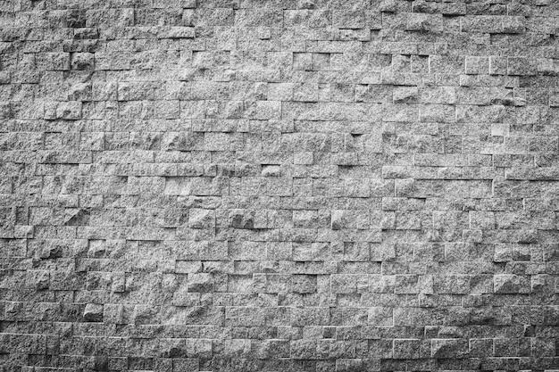 De textuur van de grijze en zwarte kleurensteenbaksteen en oppervlakte voor achtergrond Gratis Foto