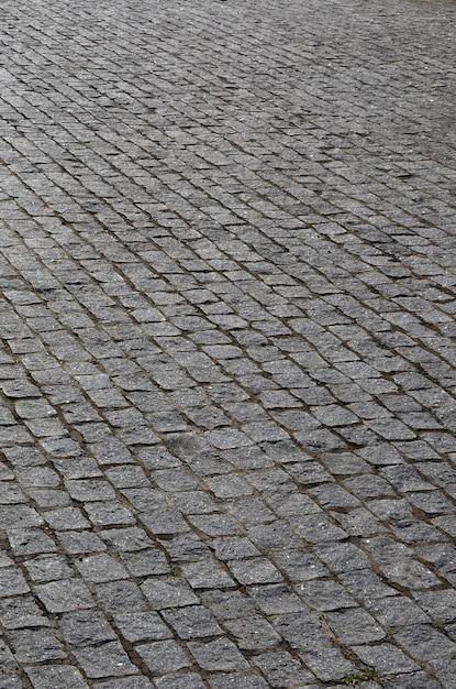 De textuur van de straatsteen (straatstenen) van veel kleine stenen van een vierkante vorm onder fel zonlicht Premium Foto