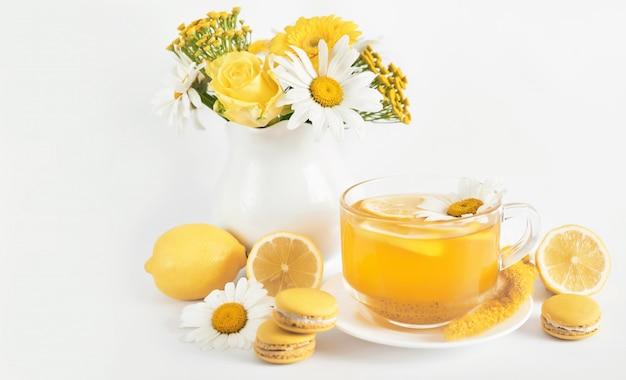 De theekop van madeliefjes met schijfje citroen en verse kamillebloemen in een vaas Premium Foto