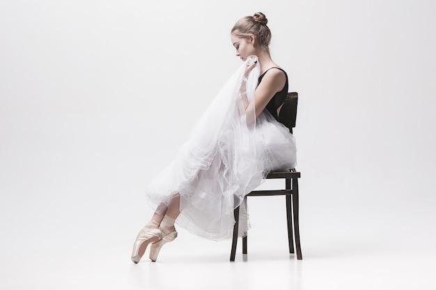 De tienerballerina in wit pak zittend op een stoel Gratis Foto