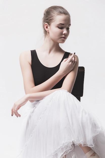 De tienerballerina in witte pakzitting op stoel Gratis Foto