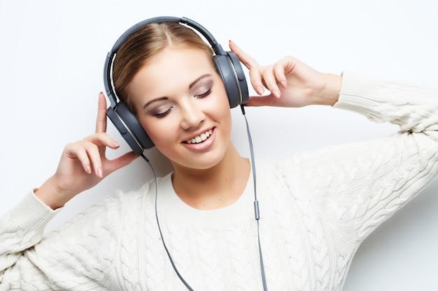 De tienermeisje dat van de muziek tegen wit danst. Premium Foto