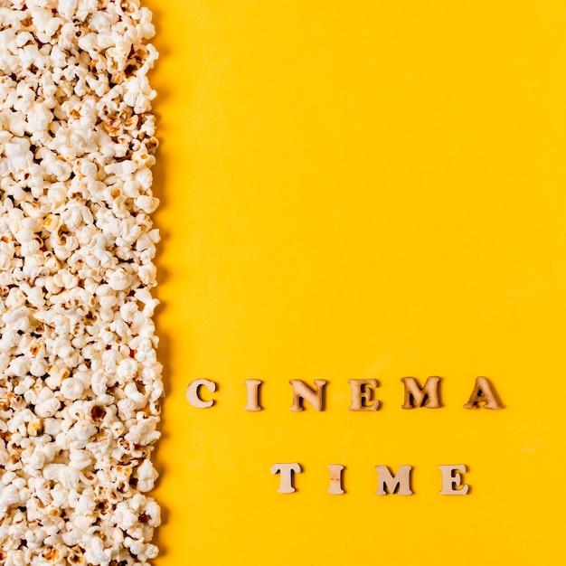 De tijdtekst van de bioskoop dichtbij popcorns op gele achtergrond Gratis Foto
