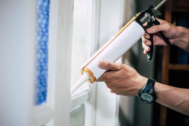 De timmerman houdt de lijm vast en hecht zich aan het raam. Gratis Foto