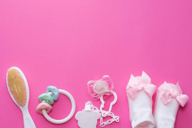 De toebehoren soother, houten stuk speelgoed, sokken en bijtring van het babymeisje op roze achtergrond met exemplaarruimte. bovenaanzicht, platliggend. Premium Foto