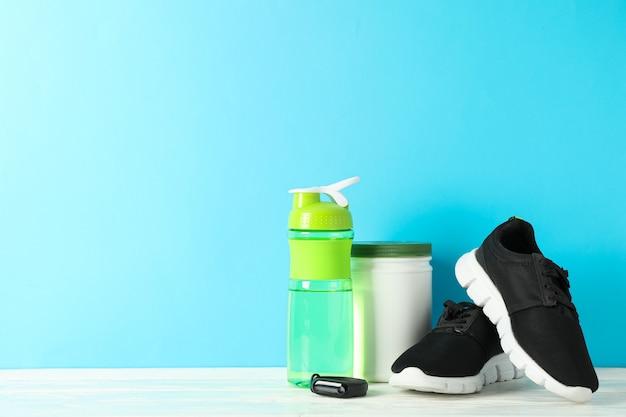 De toebehoren van de sportlevensstijl op witte houten lijst tegen blauwe achtergrond Premium Foto
