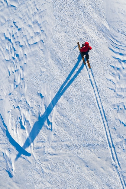 De toerist beweegt zich op ski's op de noordpool in de winter wordt van bovenaf uit de helikopter gehaald Premium Foto