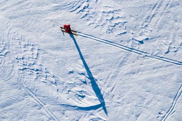 De toerist beweegt zich op ski's op een met sneeuw bedekt veld in de winter wordt van bovenaf uit de helikopter gehaald Premium Foto
