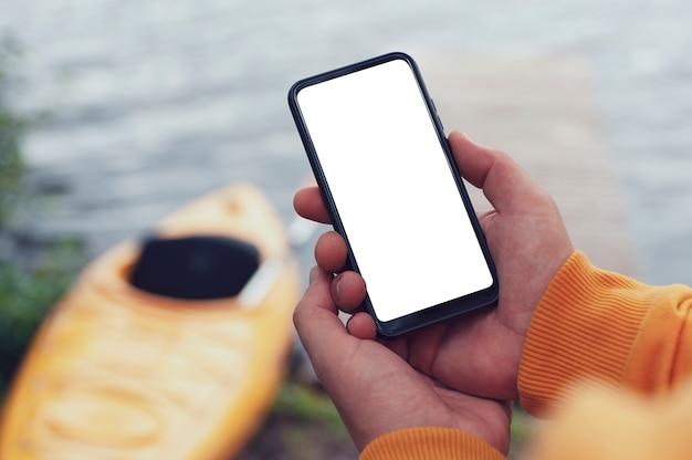 De toerist heeft een telefoon in zijn handen. bespotten smartphone close-up op de achtergrond van een kajak en een meer. Premium Foto