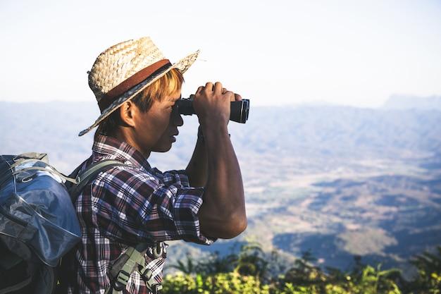 De toerist let op door verrekijkers op zonnige bewolkte hemel vanaf bergbovenkant. Gratis Foto