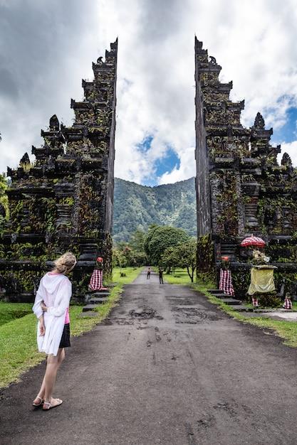 De toeristenvrouw kijkt aan traditionele balinese hindoese poorten Premium Foto