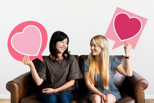 De toespraakbellen van de paarholding met hartpictogrammen Premium Foto