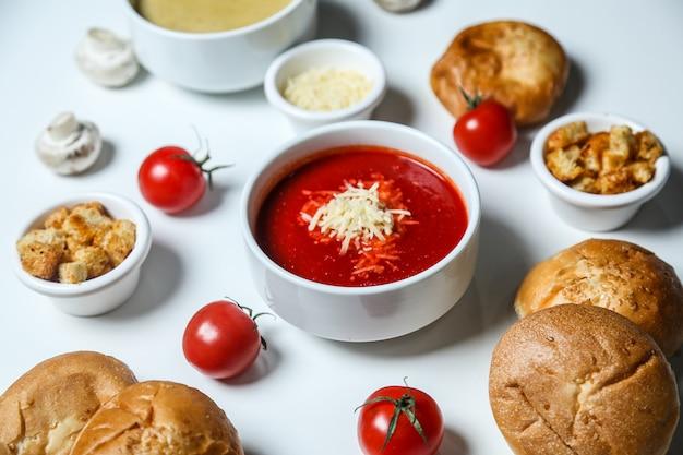 De tomatensoep van het zijaanzicht met de tomaten en het brood van kaascroutons Gratis Foto