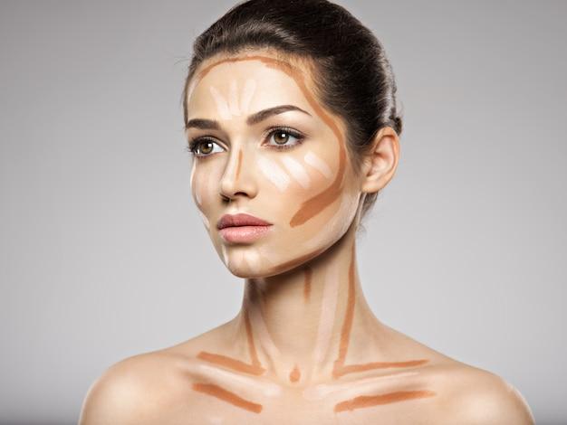 De tonale foundation van de cosmetische make-up is op het gezicht van de vrouw. schoonheidsbehandeling concept. meisje maakt make-up. Gratis Foto