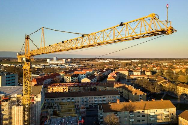 De torenkraan op heldere blauwe hemel kopieert ruimteachtergrond, stadslandschap het uitrekken zich aan horizon. drone luchtfotografie. Premium Foto