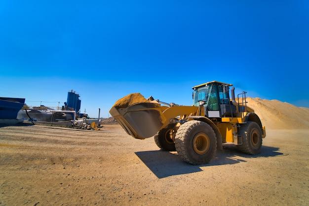 De tractor verzamelt een schep met grind. graafmachine haalt zand en grind voor de betonmix Premium Foto