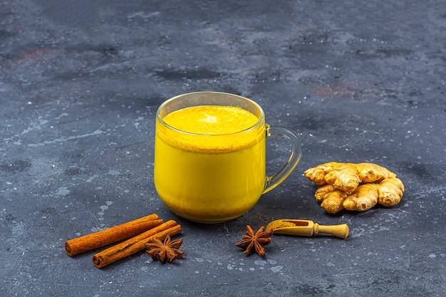 De traditionele indiër drinkt kurkumamelk is gouden melk in glasmok met kurkuma en wortelgember, kaneel, anijsster op donkere achtergrond. gewichtsverlies, gezonde en biologische drank. detailopname Premium Foto