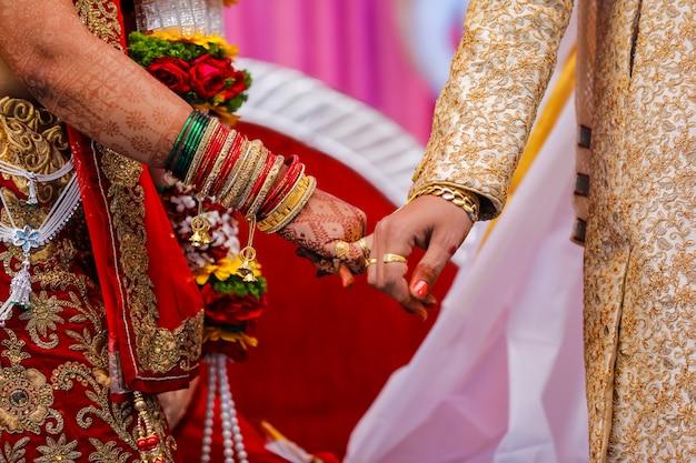 De traditionele indische huwelijksceremonie, bruidegomholding dient bruidhand in Premium Foto