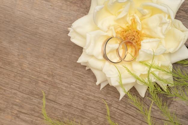 De trouwringen op wit namen op houten achtergrond toe Premium Foto