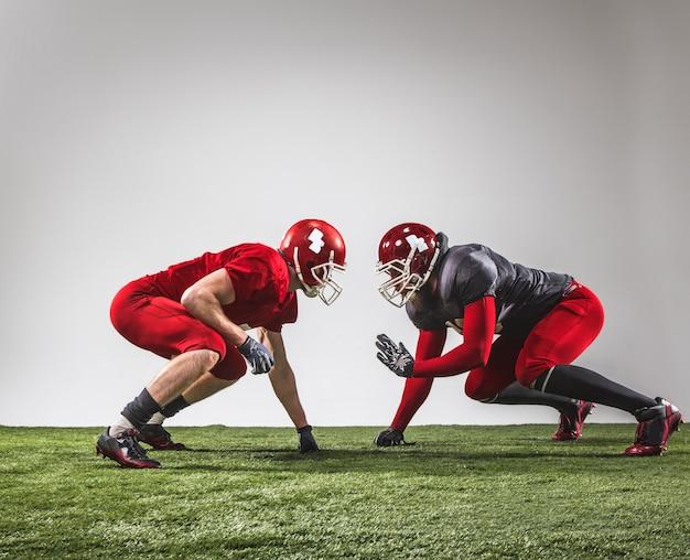 De twee amerikaanse voetballers in actie op groen gras en grijze achtergrond. Gratis Foto