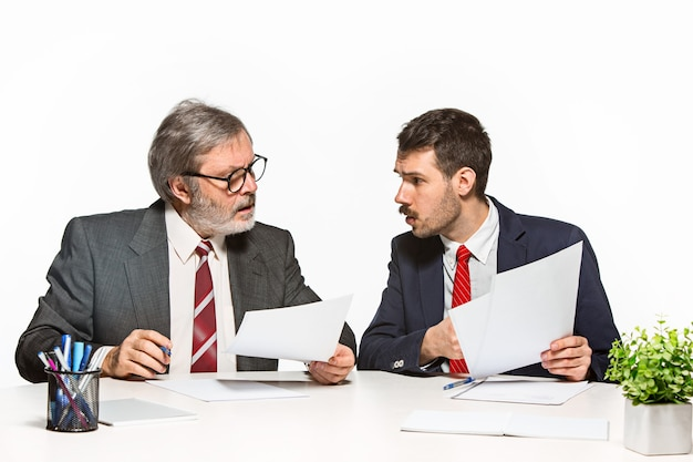 De twee collega's werken samen op kantoor op wit. Gratis Foto