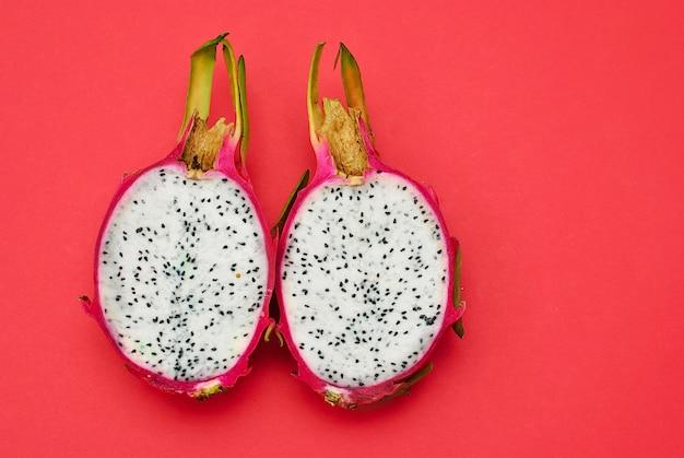 De twee helften van draakfruit op rode oppervlakte Premium Foto