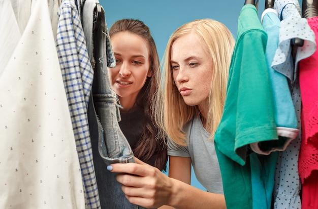 De twee jonge mooie meisjes kijken naar jurken en passen het terwijl ze kiezen in de winkel Gratis Foto